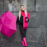 Beautiful young and happy blond woman with colorful umbrella on the street. The concept of positivity and optimism Stock Images