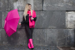 Beautiful young and happy blond woman with colorful umbrella on the street. The concept of positivity and optimism. Girl in a bright pink scarf, rubber boots Stock Photos