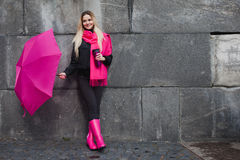 Beautiful young and happy blond woman with colorful umbrella on the street. The concept of positivity and optimism. Girl in a bright pink scarf, rubber boots Royalty Free Stock Images