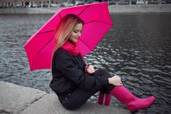 Beautiful young and happy blond woman with colorful umbrella on the street. The concept of positivity and optimism. Girl in a bright pink scarf, rubber boots Royalty Free Stock Photo