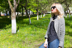 Beautiful young happy blonde girl in coat, jeans and sunglasses walking in the Park on a Sunny day Stock Photo
