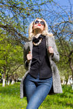 Beautiful young happy blonde girl in coat, jeans and sunglasses Stock Photography