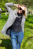 Beautiful young happy blonde girl in coat, jeans and sunglasses Royalty Free Stock Image