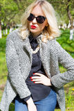 Beautiful young happy blonde girl in coat, jeans and sunglasses walking in the Park on a Sunny day Stock Photos