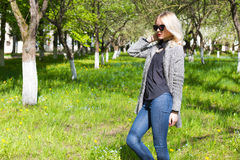 Beautiful young happy blonde girl in coat, jeans and sunglasses walking in the Park on a Sunny day Royalty Free Stock Image