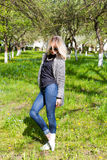 Beautiful young happy blonde girl in coat, jeans and sunglasses walking in the Park on a Sunny day Royalty Free Stock Photos
