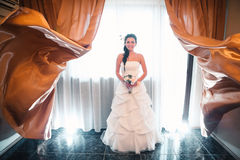Beautiful young happy  bride standing near the window. Beautiful young happy   bride standing near the window Royalty Free Stock Images