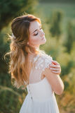 Beautiful young happy bride standing on the top of the mountain Stock Photos