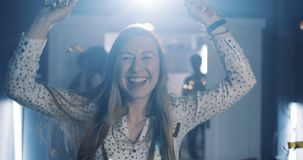 Beautiful young happy caucasian woman blows on confetti, making a wish at magic birthday party celebration slow motion. Cheerful female student relaxing stock footage