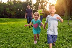 Beautiful happy children walking with parents in park. Beautiful young happy children walking with parents in park stock images