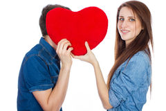 Beautiful young happy couple kissing behind a red heart, holding it in hands, isolated on a white background Royalty Free Stock Photography
