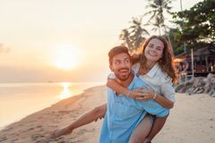 Beautiful young happy couple in love having fun on the beach at sunset during the honeymoon vacation travel, the guy carries the royalty free stock photography