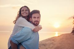 Beautiful young happy couple in love having fun on the beach at sunset during the honeymoon vacation travel, the guy carries the stock photos