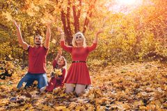 Beautiful young happy family throwing leaves in autumn day. stock images
