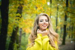 Beautiful young happy girl with bright red-yellow leaf in park. Beautiful fashion woman in autumn red dress with falling. Leaves over nature background. Dreamy royalty free stock photos