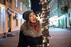 Beautiful young happy girl on the streets of a nighty city with lights in winter