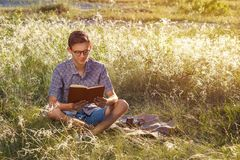 Beautiful young happy guy with glasses outdoors reading a book on a Sunny day royalty free stock photography