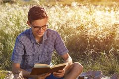 Beautiful young happy guy with glasses outdoors reading a book on a Sunny day stock photography