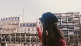 Beautiful young happy tourist woman smiling, pointing at sunny Eiffel Tower view at Paris apartment balcony slow motion. stock video
