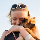Beautiful young happy woman with blonde hair holding small dog Royalty Free Stock Photography