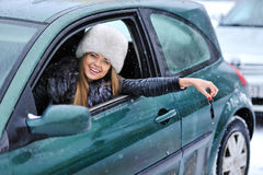 Beautiful young happy woman in car showing the keys - outdoors Stock Image