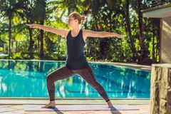 Beautiful young happy woman doing yoga exercise near swimming pool. Healthy lifestyle and good wellness concepts.  stock images