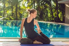 Beautiful young happy woman doing yoga exercise near swimming pool. Healthy lifestyle and good wellness concepts stock photo