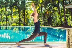 Beautiful young happy woman doing yoga exercise near swimming pool. Healthy lifestyle and good wellness concepts.  royalty free stock images