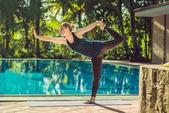 Beautiful young happy woman doing yoga exercise near swimming pool. Healthy lifestyle and good wellness concepts.  stock photos