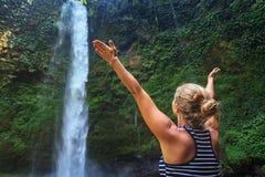 Beautiful young happy woman enjoying nature under tropical fresh waterfall Royalty Free Stock Photography