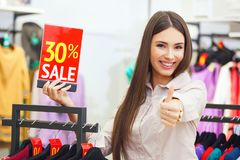 Beautiful young happy woman holiding red sale sign in a clothing Royalty Free Stock Image