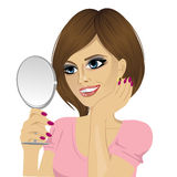 Beautiful young happy woman looking at herself in small mirror Royalty Free Stock Photography