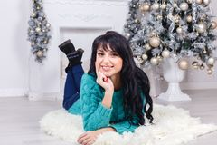 Beautiful young happy woman lying on a floor indoors in christma Royalty Free Stock Images