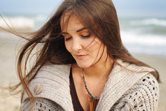 Beautiful young happy woman portrait against seascape, long hair fluttering in the wind, looking at camera, casual autumn fashion Royalty Free Stock Photo