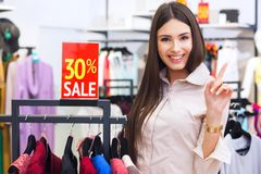 Beautiful young happy woman with red sale sign in a clothing sto Royalty Free Stock Images
