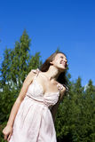 Beautiful young happy woman under blue sky. Royalty Free Stock Photography