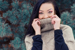 Beautiful young happy woman winter day in the forest near trees hides his face under jacket royalty free stock photo