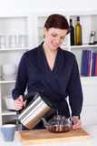 Beautiful happy young woman preparing tea at home Stock Images