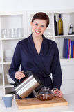 Beautiful happy young woman preparing tea at home Royalty Free Stock Photography