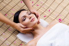 Beautiful, young and healthy woman on bamboo mat in spa salon having face massage. Stock Photos