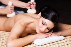 Beautiful, young and healthy woman on bamboo mat in spa salon is having massage. Royalty Free Stock Image