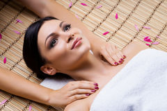 Beautiful, young and healthy woman on bamboo mat in spa salon having shoulders massage. Royalty Free Stock Images