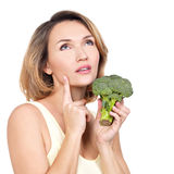 Beautiful young healthy woman holds broccoli. Royalty Free Stock Photography