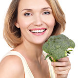 Beautiful young healthy woman holds broccoli. Royalty Free Stock Images