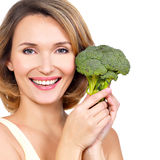 Beautiful young healthy woman holds broccoli. Royalty Free Stock Image