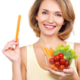 Beautiful young healthy woman with a plate of vegetables. royalty free stock photo