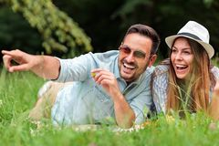 Beautiful young heterosexual couple having a great time during picnic in a park stock photos