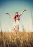 Beautiful young hippie girl dancing in the field at sunset time Royalty Free Stock Photography