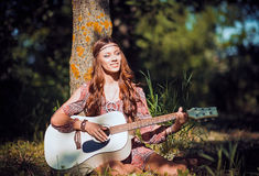 Beautiful young hippie girl sitting under the tree and playing the guitar Stock Images