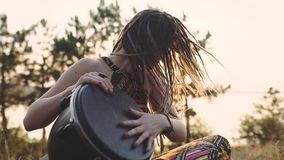 Beautiful young hippie woman with dreadlocks playing on djembe. Funky woman drumming in nature on an ethnic drum at sunset or sunr
